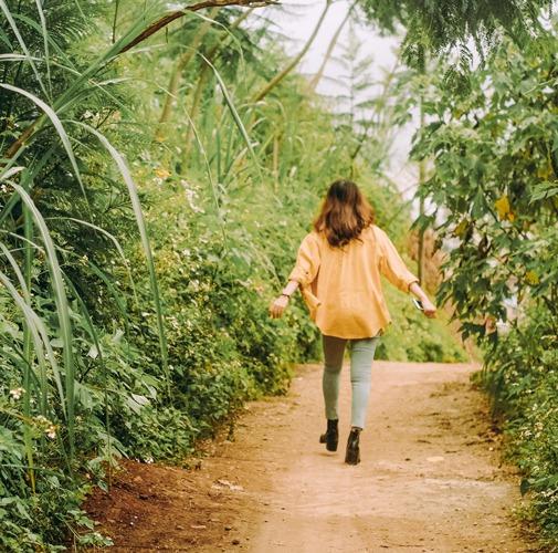 An asian woman wearing a yellow shirt walks joyfully down a bright nature path