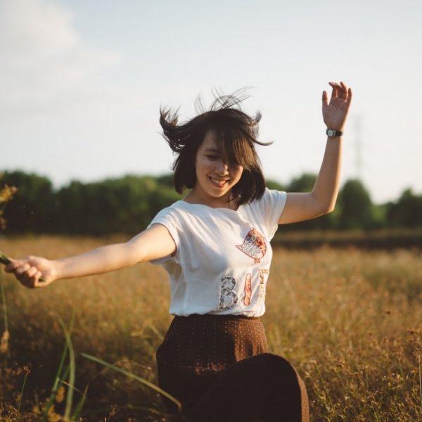 Happy woman dancing in field.
