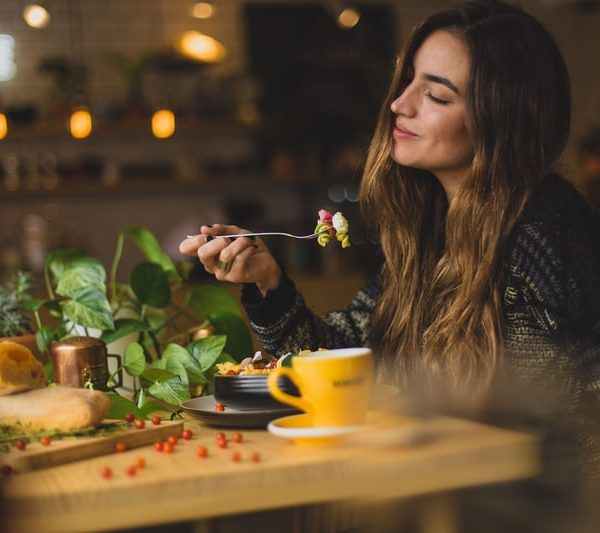 Woman eating healthy food happily and mindfully.
