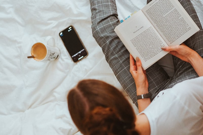 Woman reading book in bed, setting boundaries with phone.
