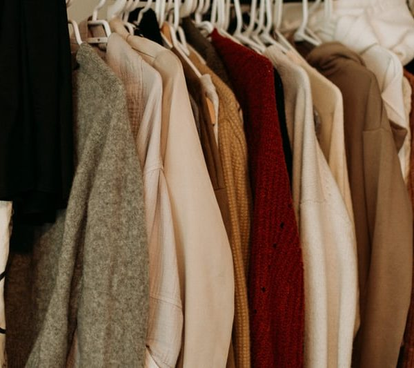 Organizing clothing in closet for sustainable fashion choices.