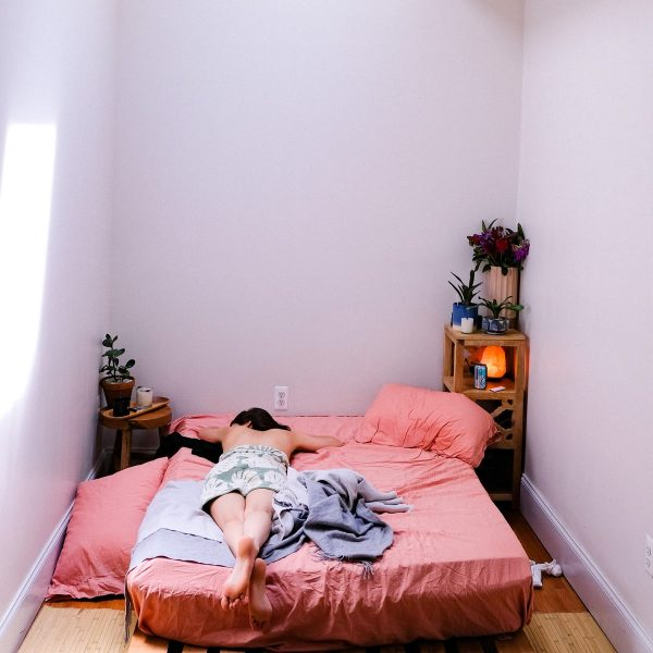 Woman lying in bed in a cozy room.